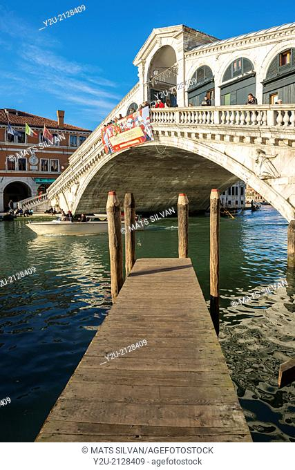 Rialto bridge and a pier with blue sky in Venice Italy