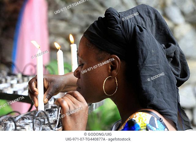 African woman lighting candles in church