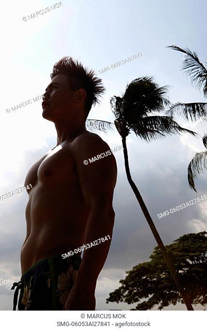 profile shot of shirtless man looking at sky