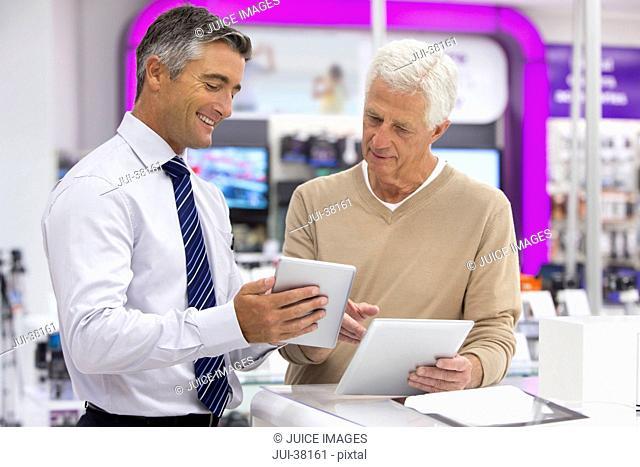 Smiling salesman showing senior man digital tablets in electronics store