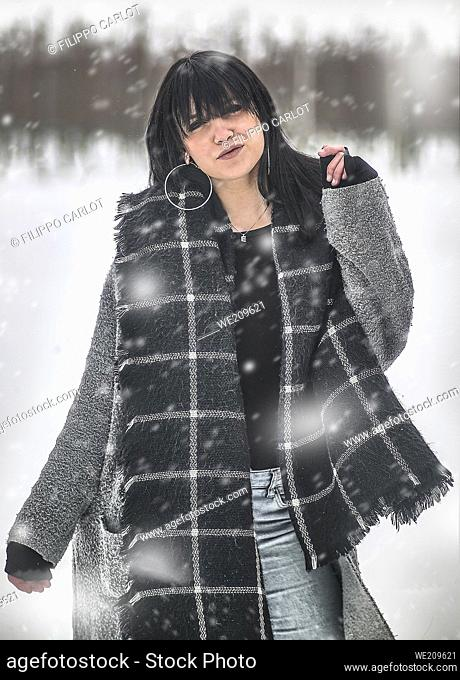 Vertical shot of a portrait of a young dark-haired girl walking relaxed under the snow