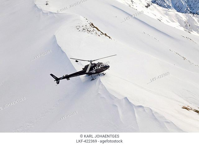 Helicopter landing with skiers and snowboarders in deep snow, Winter sport, Heliskiing, South Island, New Zealand