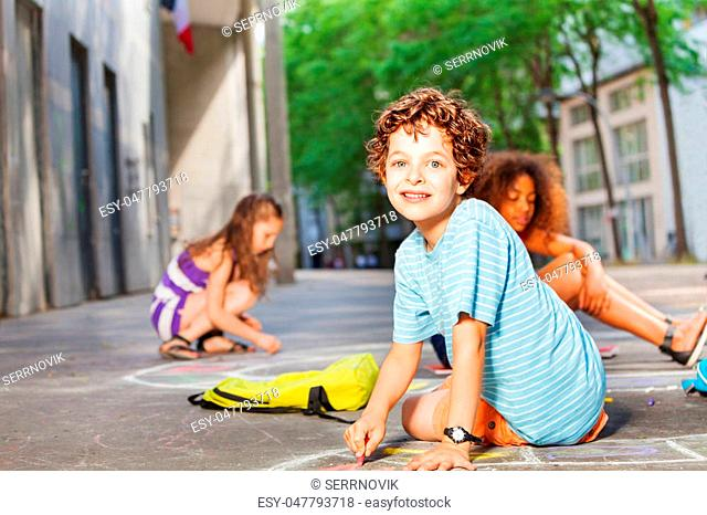 Portrait of a boy with friends draw numbers for hopscotch game on the street