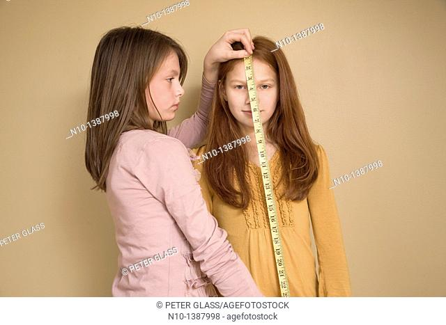 Preteen girl measuring her friend with a tape measure