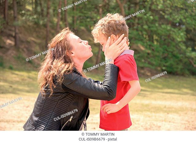 Young woman kissing son on wooded beach