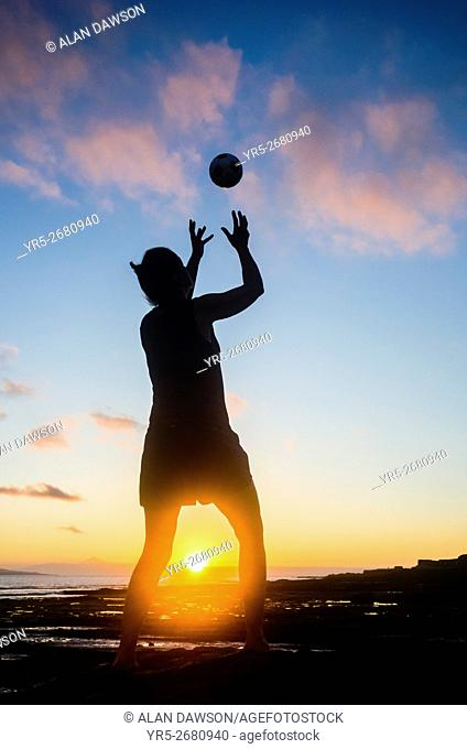 Woman playing Handball at sunset on El Confital beach in Las Palmas, Gran Canaria, Canary Islands, Spain