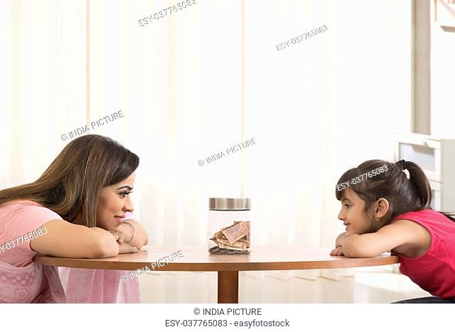 Mother and daughter leaning on table looking at money box
