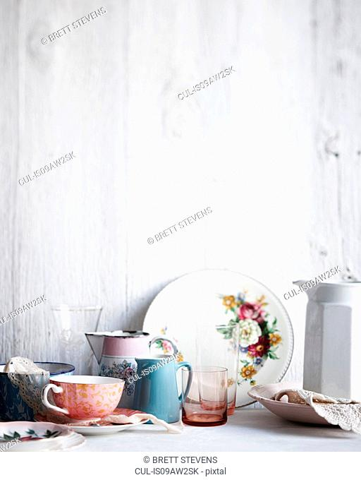 Variety of drinking glasses, plates and jugs on whitewashed table