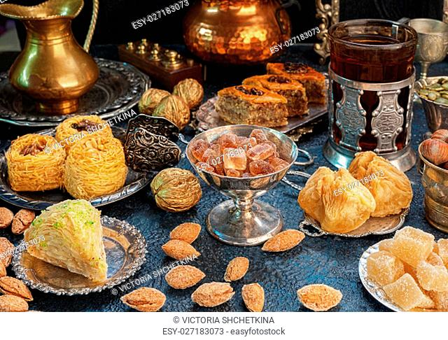 Large set of Eastern, Arab, Turkish sweets with cup of tea