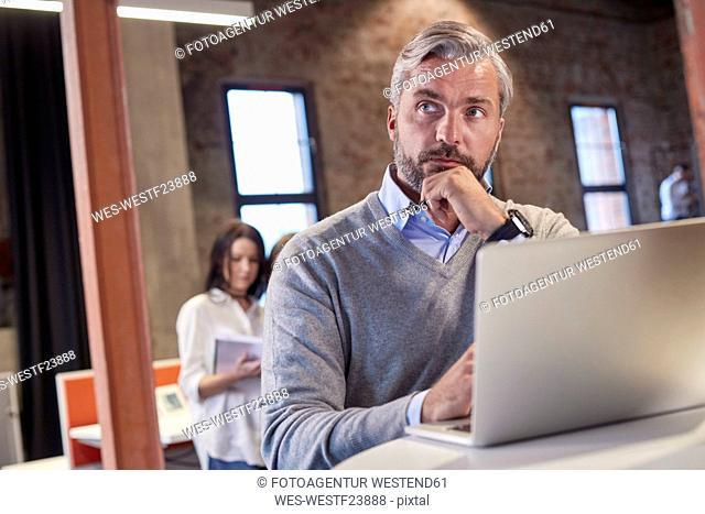 Mature man sitting at laptop, thinking