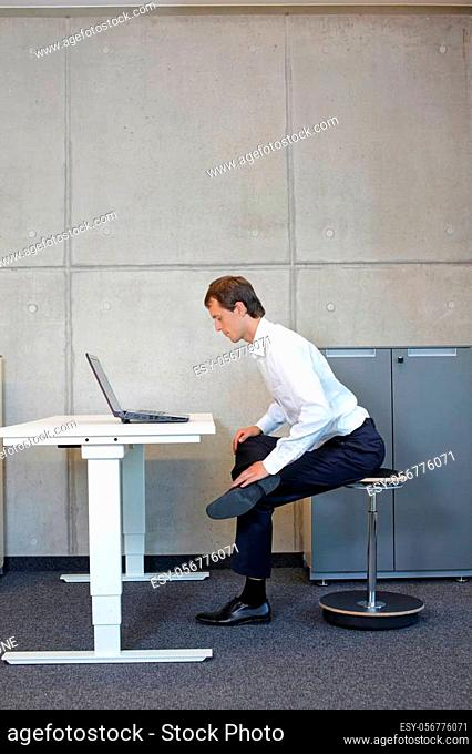 Business man exercising on pneumatic leaning seat with laptop at electric height adjustable desk in office - stretching at desk