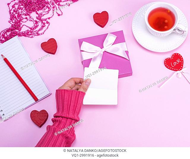 female hand holding blank white paper business cards over a table with a cup of tea, top view