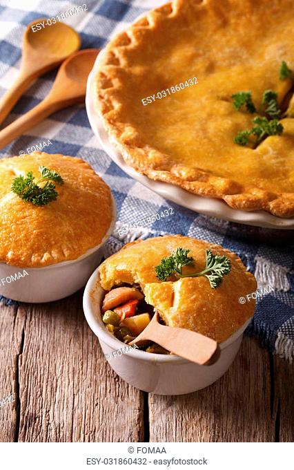 American cuisine: chicken pie with vegetables in a pot close-up on the table. vertical