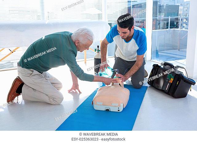 Paramedics practicing cardiopulmonary resuscitation on mannequin