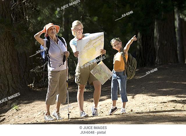 Girl 7-9 hiking on woodland trail with mother and grandmother, pointing, woman consulting map, smiling