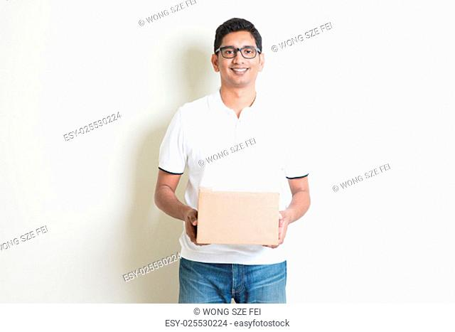 Indian man smiling and holding a courier box standing on plain background with shadow. Asian handsome guy model
