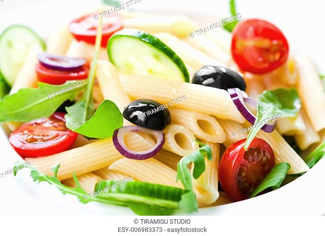 Pasta salad with tomato, black olives and arugula