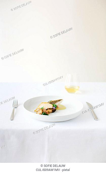 Table setting with plate of fish and mushrooms