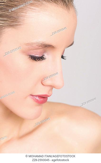 Attractive young woman with pink eyeshadow eyes closed