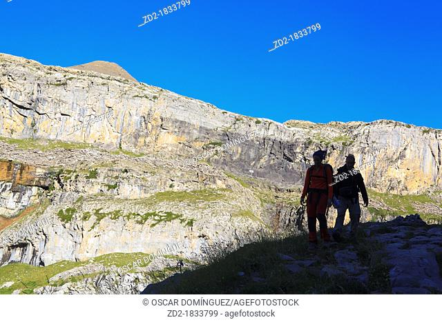 Hikers silhouetted in front of cliffs and Tobacor peak in Ordesa valley  Ordesa and Monte Perdido National Park  Pyrenees  Huesca  Aragon  Spain
