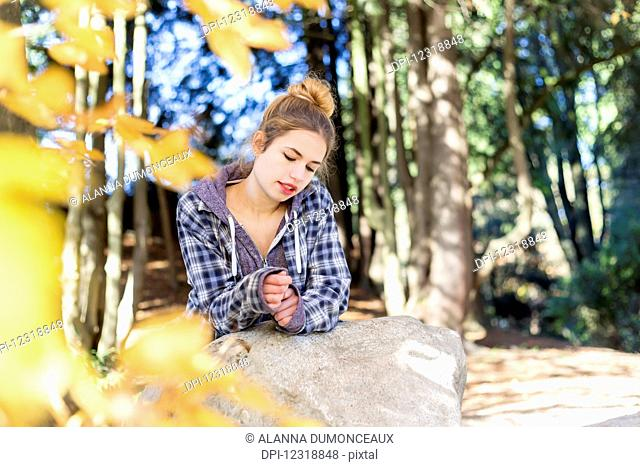 This young teenage girl hangs out alone in a park, sitting on a rock in a thoughtful disengaged position thinking to herself; New Westminster, British Columbia