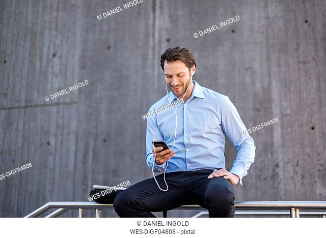 Smiling businessman with earbuds sitting on a railing looking at smartphone