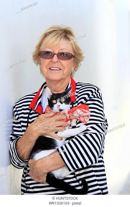 Senior woman smiling holding therapy cat