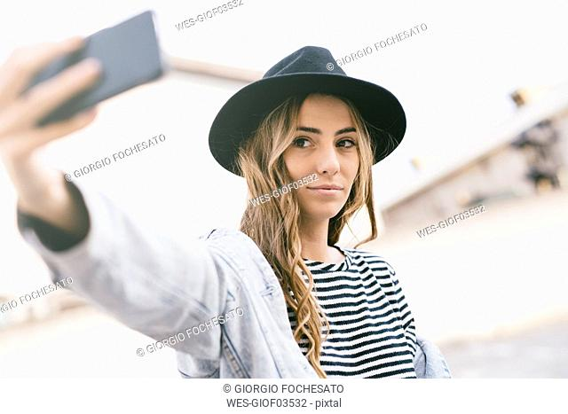 Portrait of fashionable young woman wearing hat taking selfie with smartphone