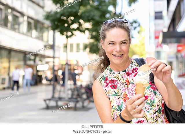 Portrait of smiling mature woman with ice cream cone in the city
