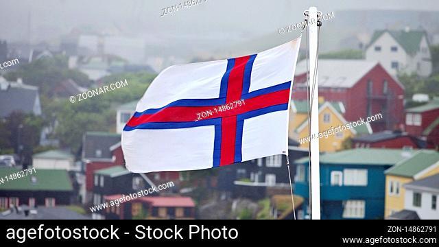 Flagge der Faeroeer vor Haeusern im Nebel, Thórshavn, Streymoy, Faeroeer, Føroyar, Daenemark, Europa
