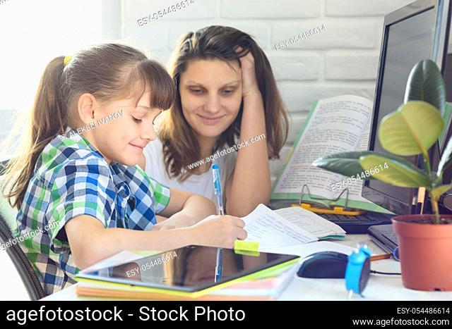 Girl and mom do a computer job at home