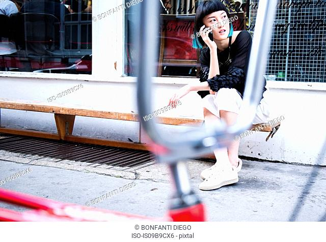 Young stylish woman sitting outside shop making smartphone call
