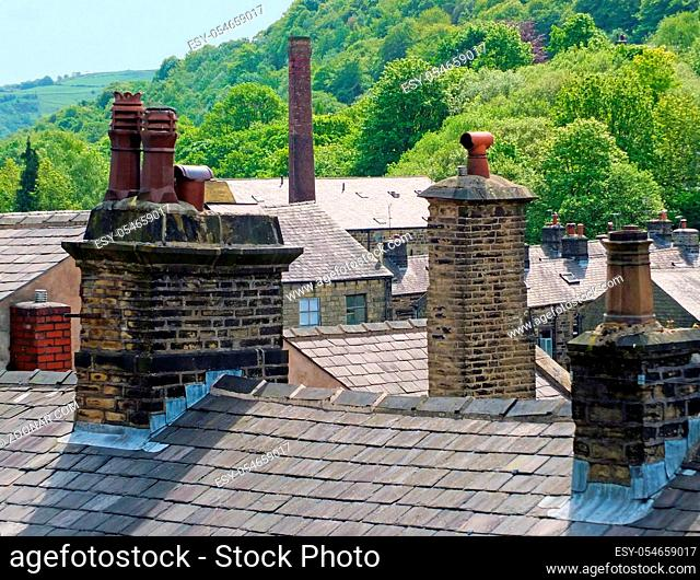 chimneys and roofs of traditional stone build houses and mills typical of west yorkshire small towns and villages set against steep valley woodland with blue...