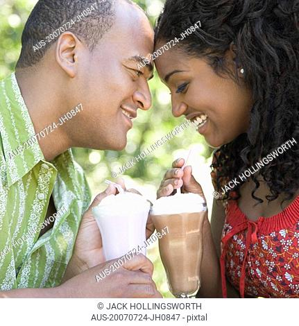 Close-up of a mid adult man and a young woman holding glasses of milkshake