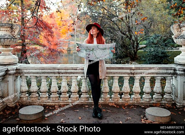 Woman wearing hat holding map while leaning on railing against lake in park