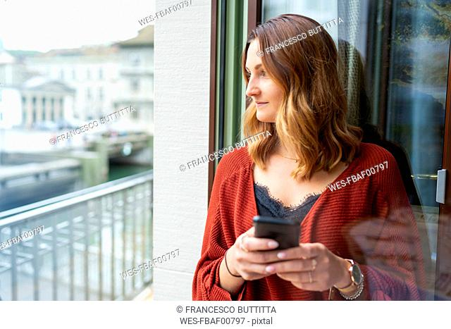 Young woman using cell phone at the balcony door