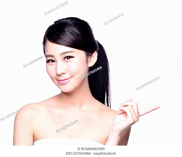 Beautiful young woman with healthy clean skin show something on her hand. Isolated on white. asian beauty
