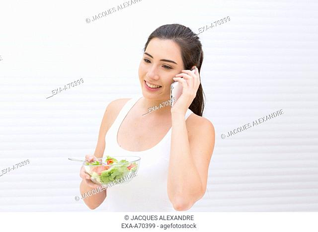 woman eating salad, phone call