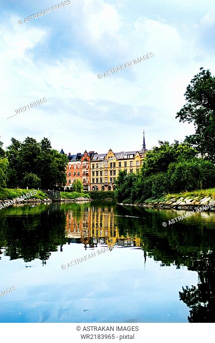 Reflection of trees and buildings on calm river in city