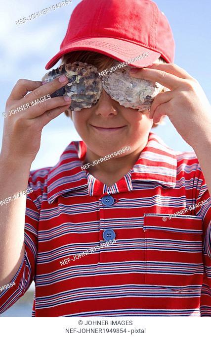 Boy covering his eyes with shells, Vastkusten, Sweden