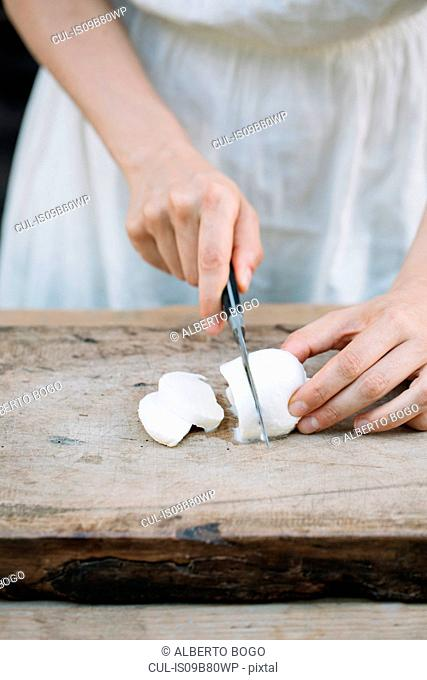 Woman slicing mozzarella on chopping board, mid section