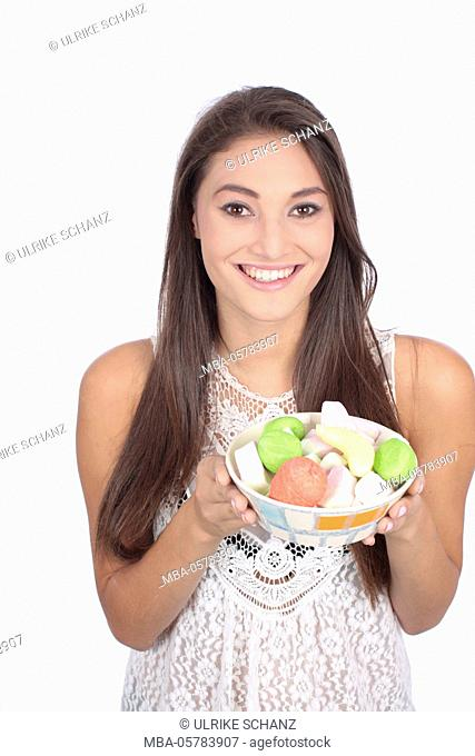 Young woman, smiling, bowl, sweets, holding, half portrait, studio