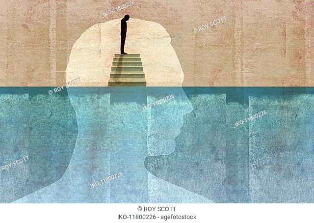 Man on top of staircase looking down inside of half submerged profile of man's head