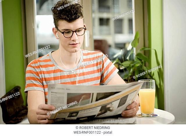 Germany, Bavaria, Munich, Young man reading newspaper in cafe