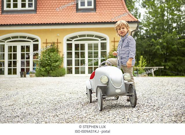 Boy playing with vintage toy car in front of house