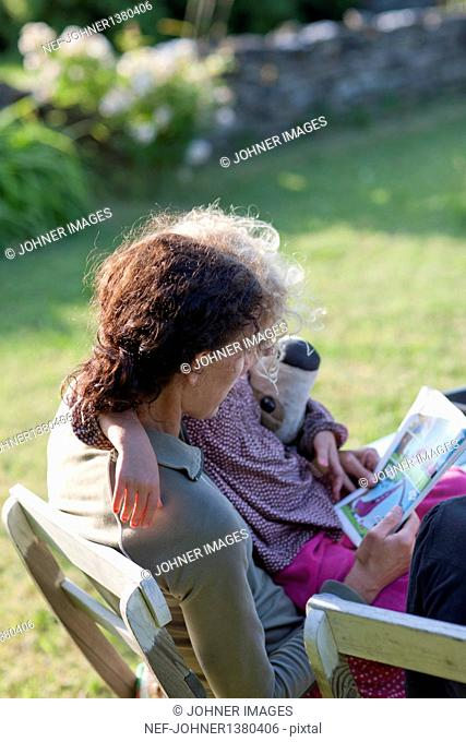 Mother and daughter reading book on lounge chair