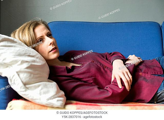Tilburg, Netherlands. Young adult woman resting an afternoon on her living room couch