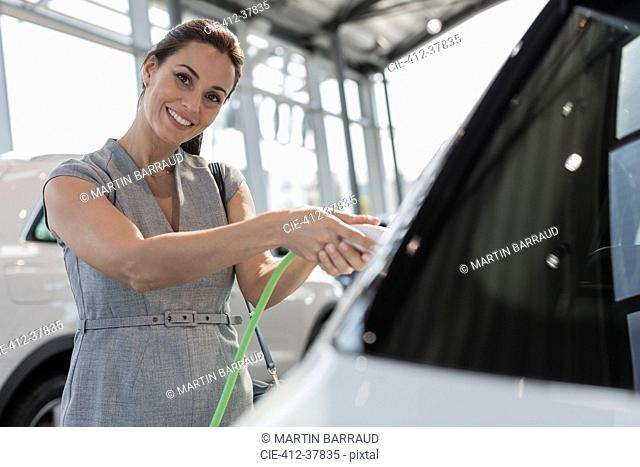 Portrait smiling, confident female customer charging hybrid car in car dealership showroom