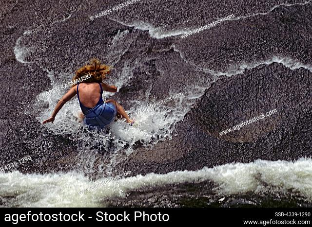 Woman sliding on rocks wetted by a waterfall in North Carolina's Pisgah National Forest