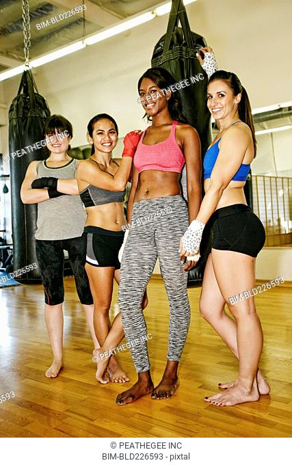 Smiling women standing near heavy bag in gymnasium